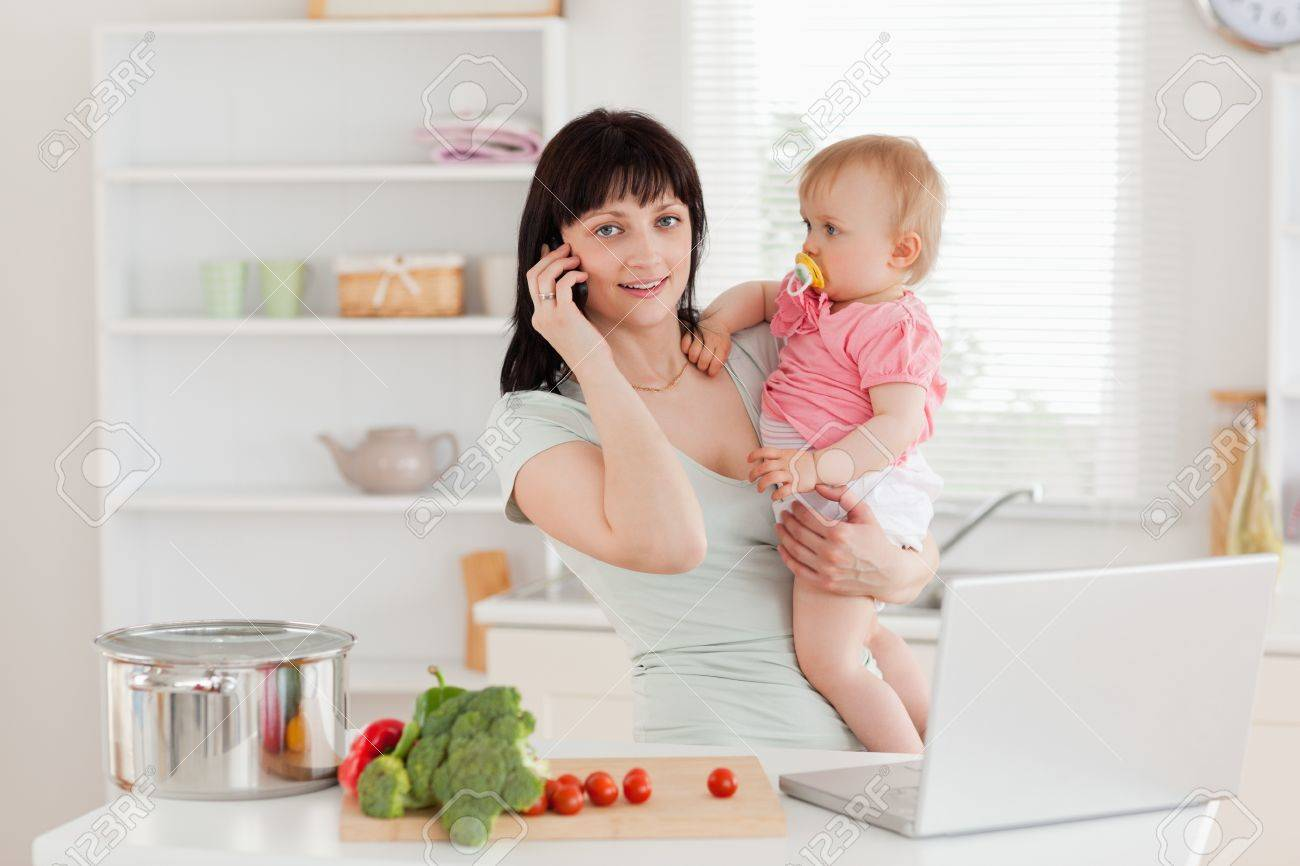 Charming brunette woman on the phone while holding her baby in her arms in the kitchen Stock Photo - 10070859