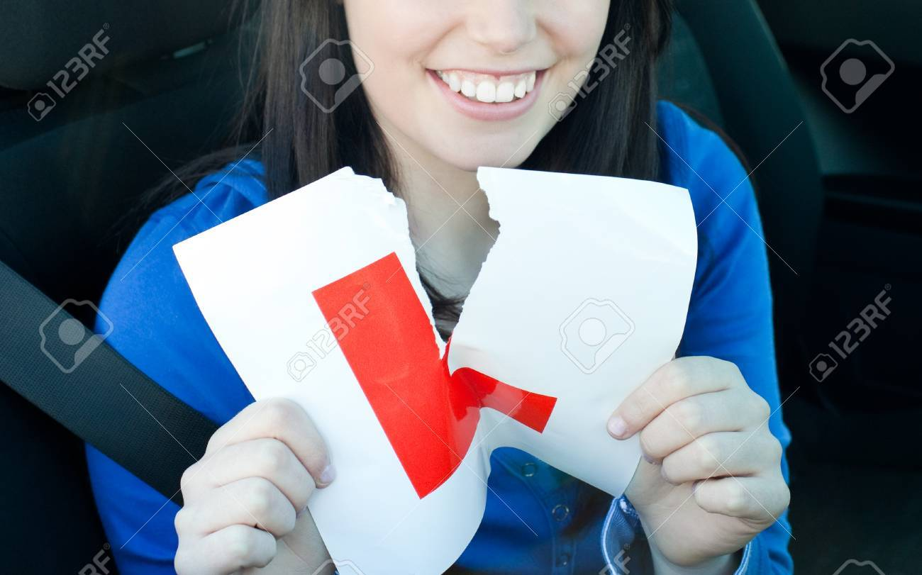 Charming teen girl sitting in her car tearing a L-sign Stock Photo - 10075327