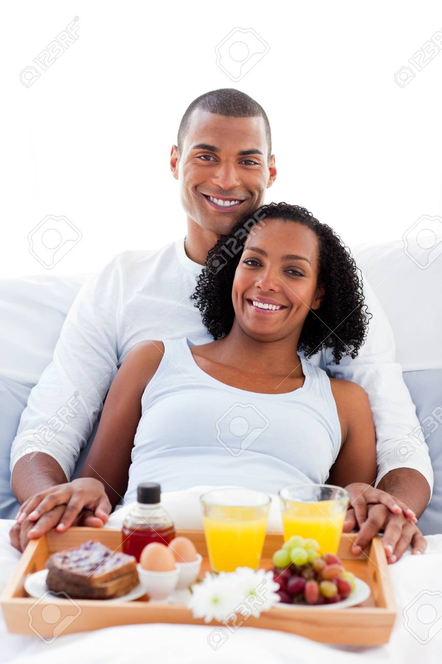 Afro-american couple having breakfast lying on their bed Stock Photo - 10093306