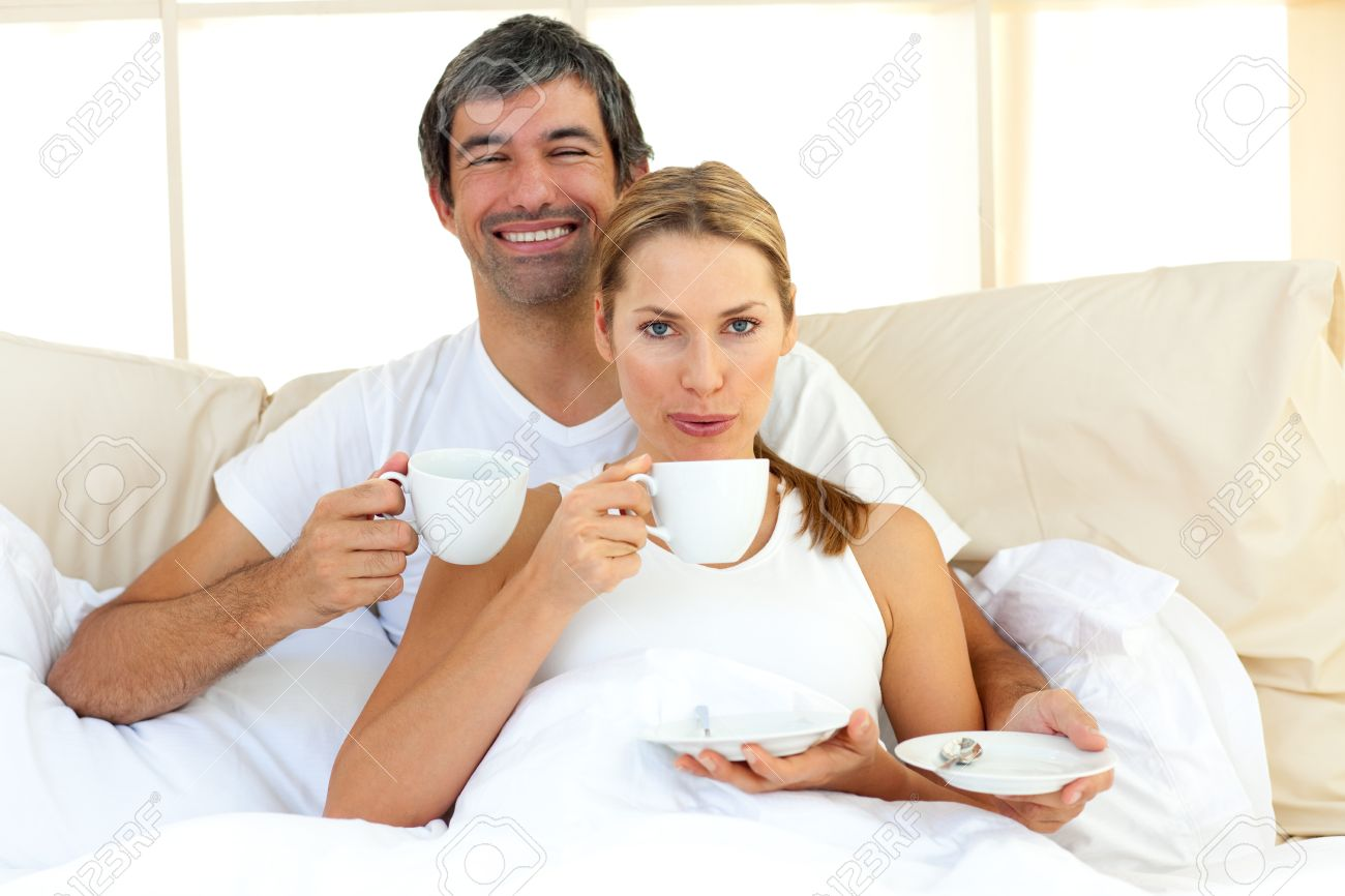 Intimate couple drinking coffee lying in the bed Stock Photo - 10093064