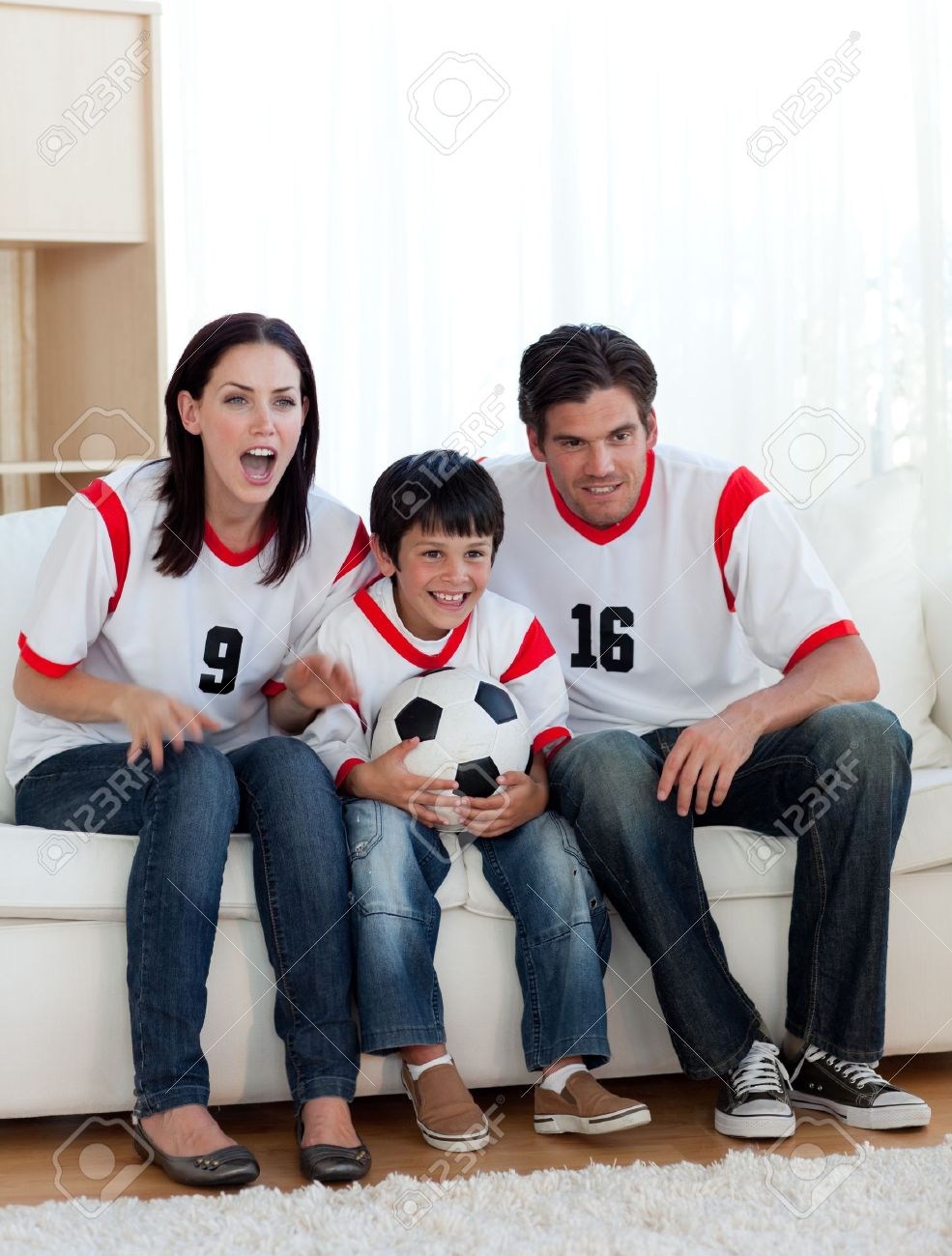 Parents and their son watching a football match Stock Photo - 10095353