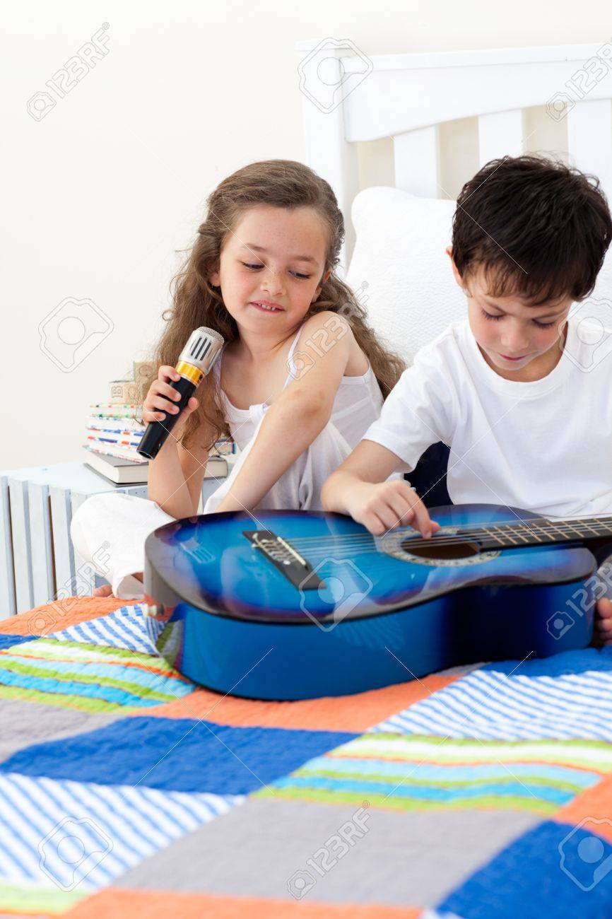 Brother and sister having fun with a guitar Stock Photo - 10095305
