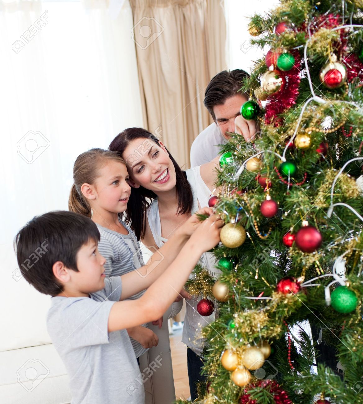 Happy family decorating a Christmas tree with boubles Stock Photo - 10107210
