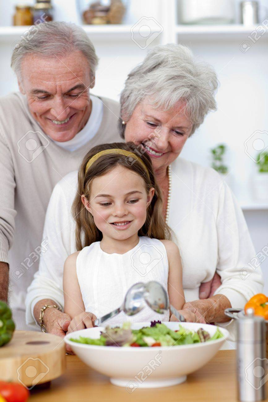 Happy grandparents eating a salad with granddaughter Stock Photo - 10095378