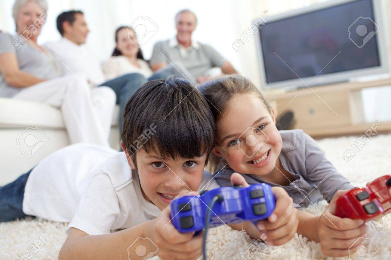 Children playing video games on floor and family on sofa Stock Photo - 10110807