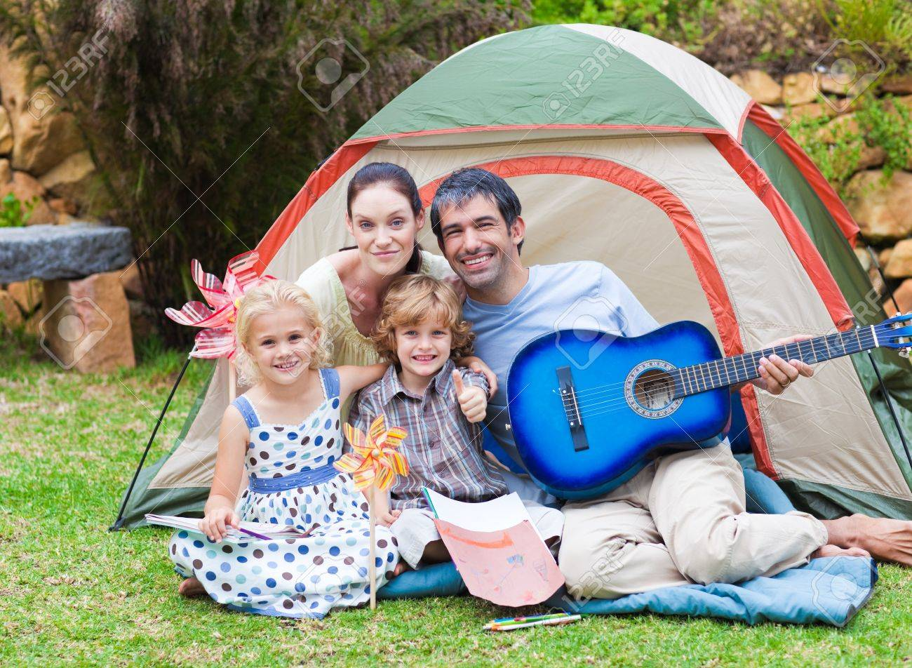Family playing a guitar in a tent Stock Photo - 10070439