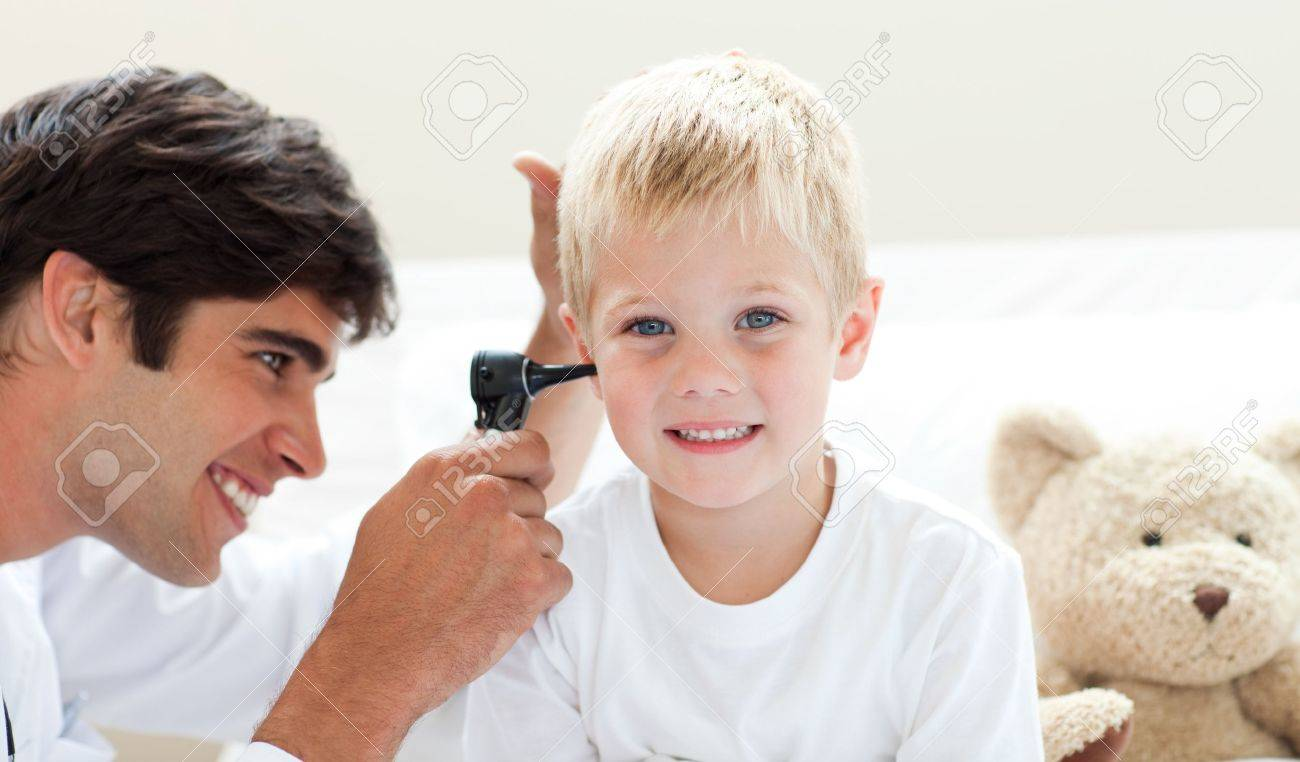 Attractive doctor checking his patient's ears Stock Photo - 10110960