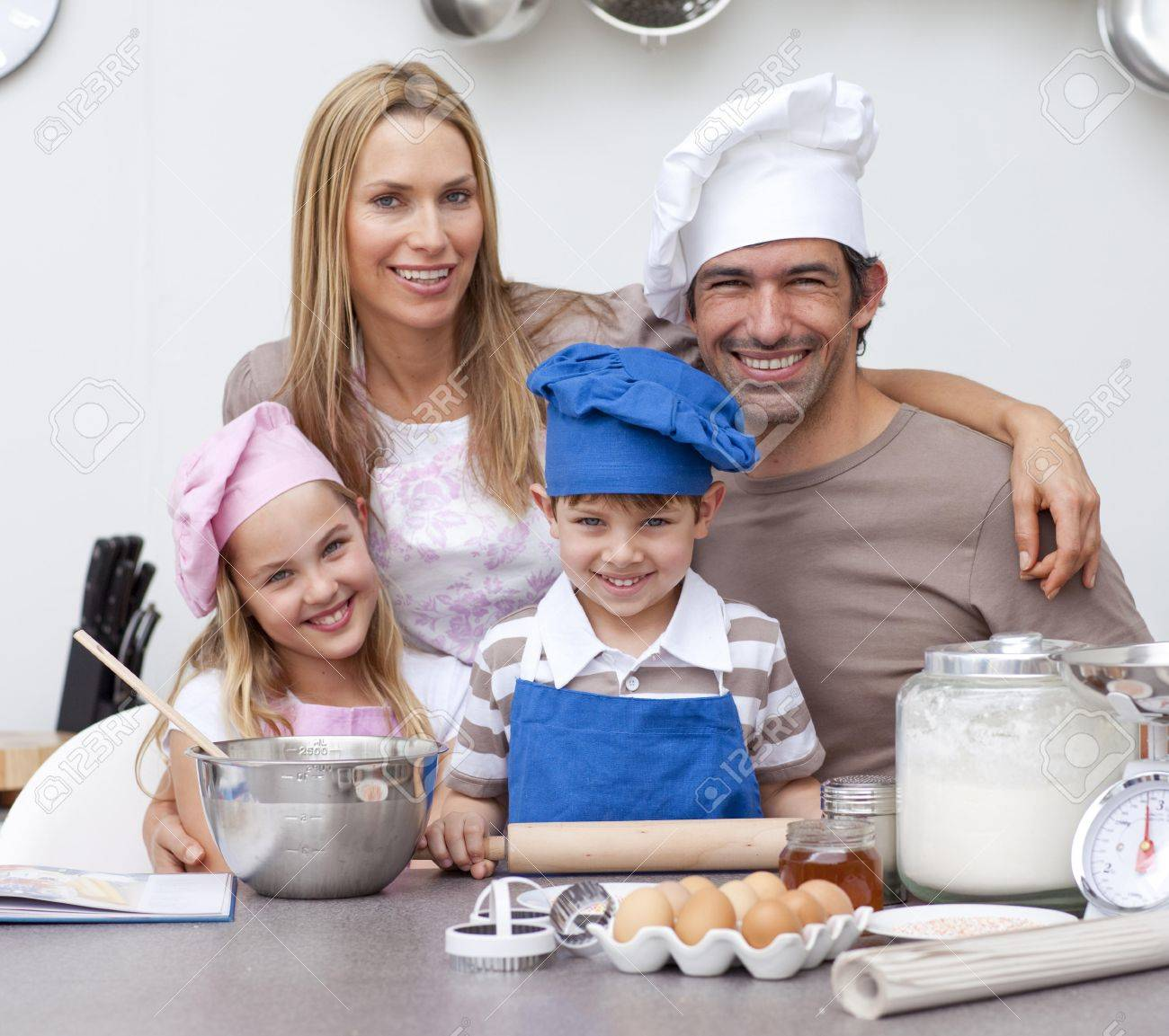 Smiling parents helping children baking in the kitchen Stock Photo - 10110864