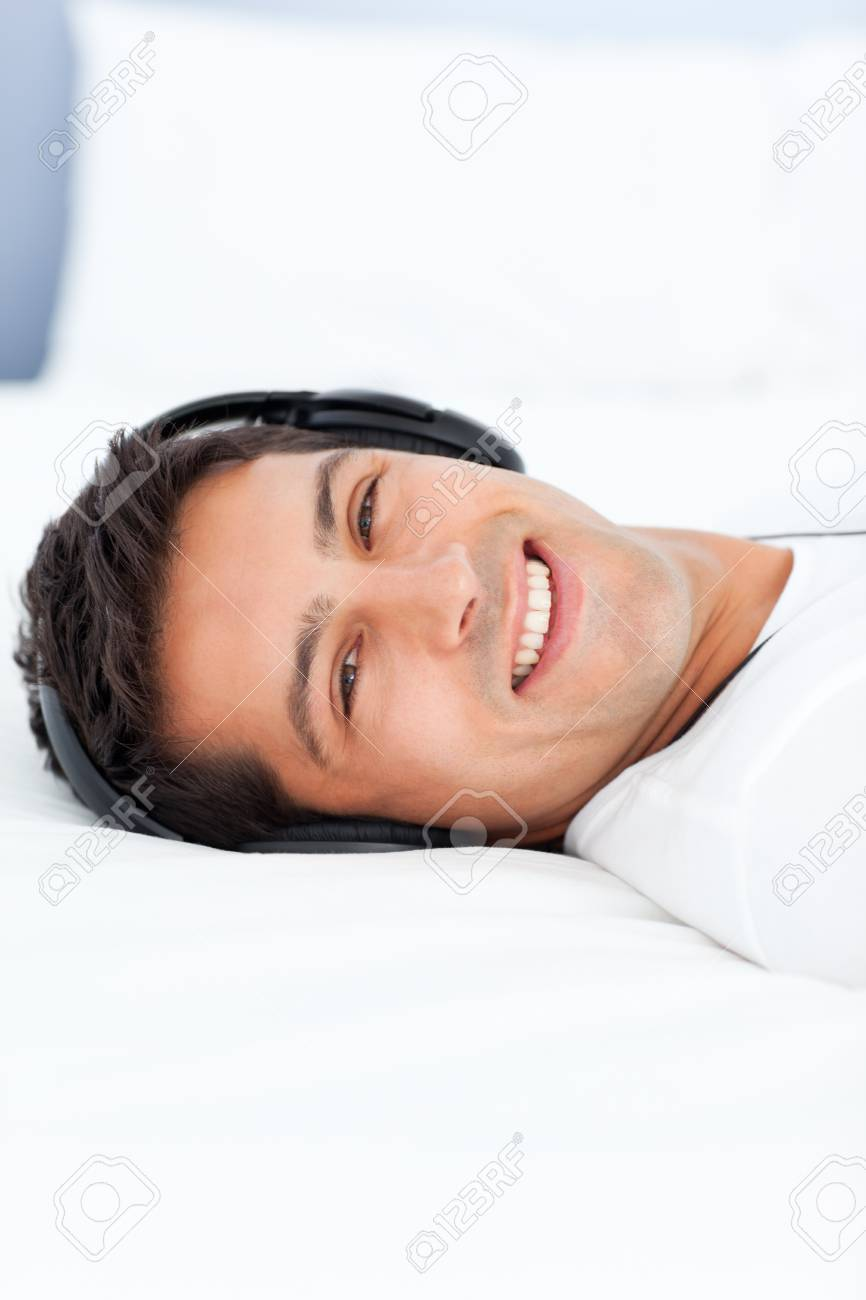Cheerful man listening music with headphones lying on his bed Stock Photo - 10212519
