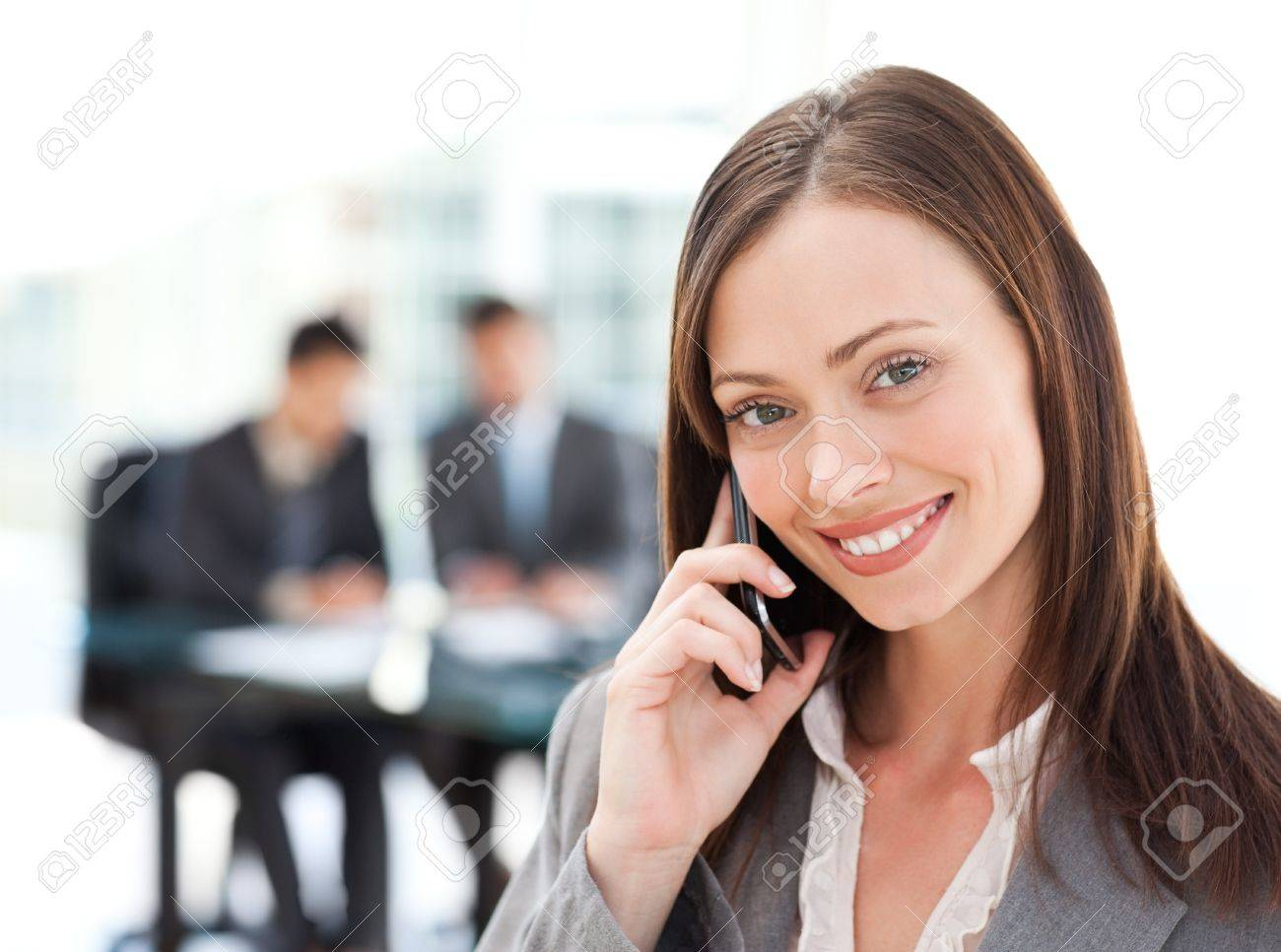Captivating businesswoman on the phone while her team is working Stock Photo - 10213632