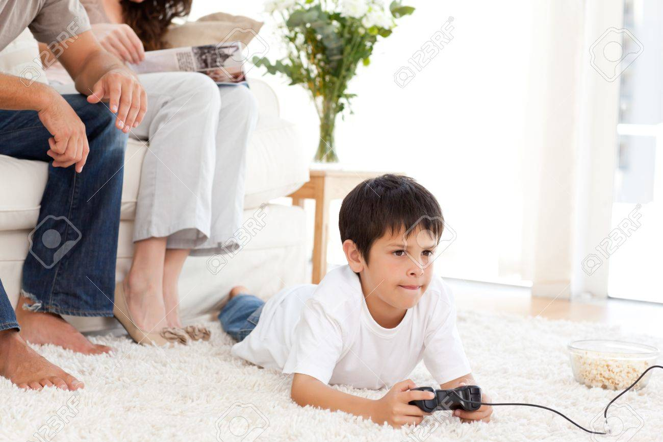 Cute boy playing video game lying on the floor at home Stock Photo - 10215594