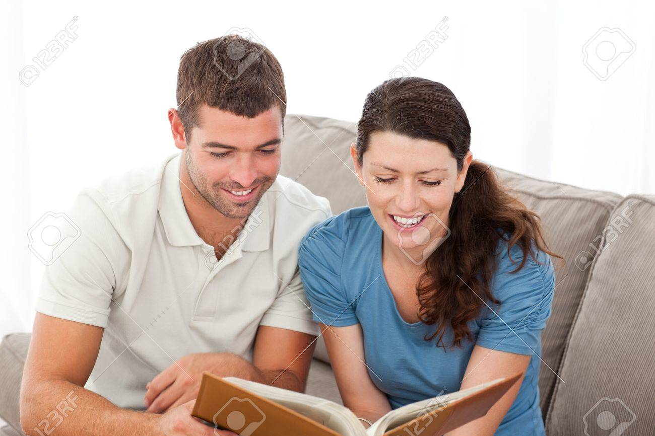 Lovely couple reading a book together on the sofa Stock Photo - 10220343