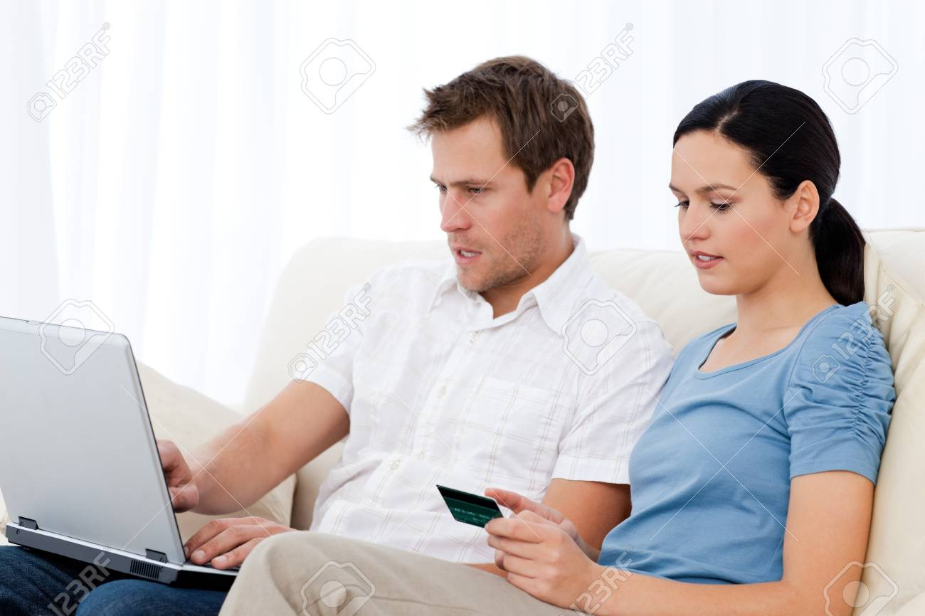 Pretty woman reading code on a credit card for his boyfriend Stock Photo - 10172383