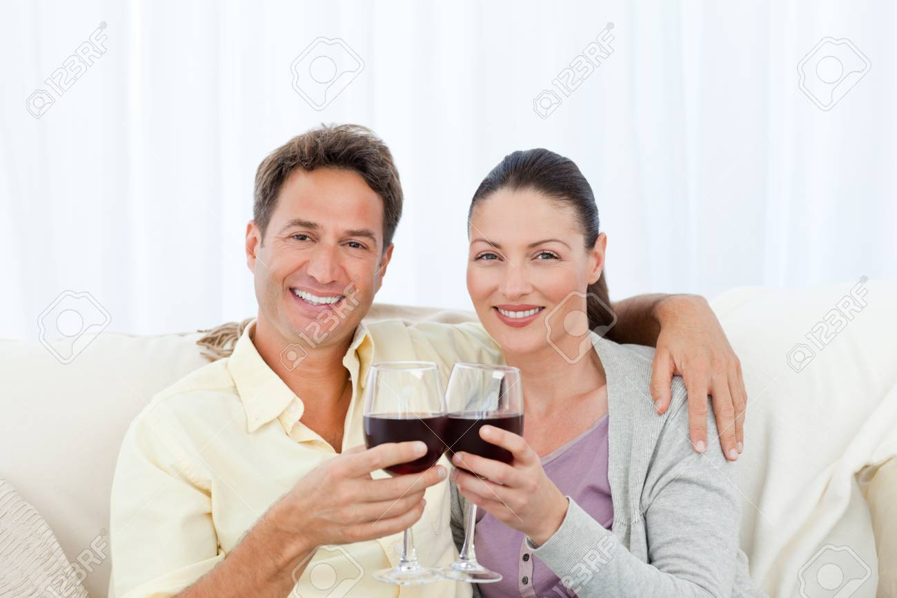 Portrait of a couple clinking glasses of red wine on the sofa Stock Photo - 10194458