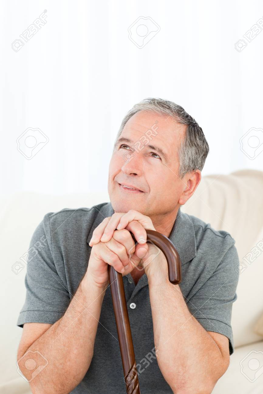 Mature man thoughtful with his walking stick on his bed at home Stock Photo - 10219598