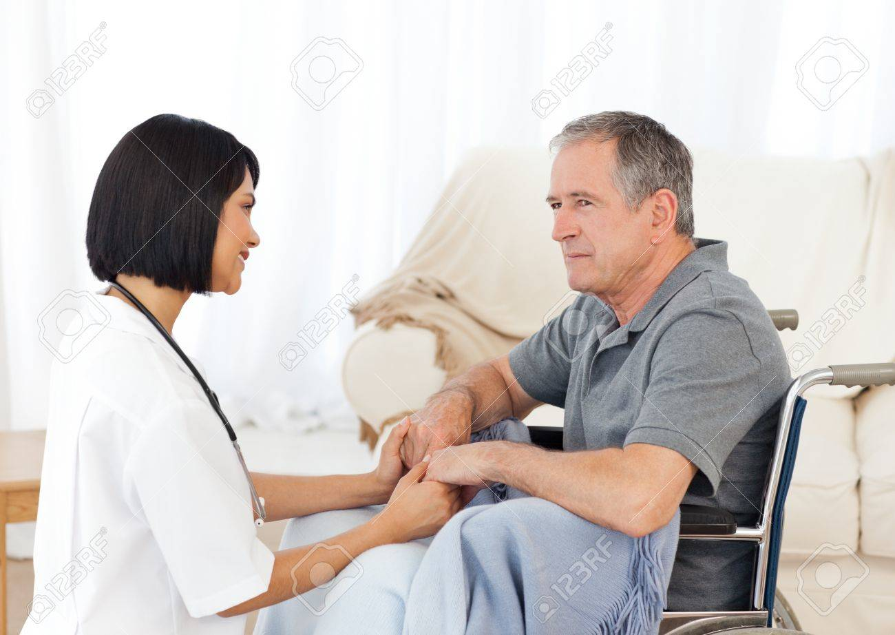 Man in his wheelchair with his nurse at home Stock Photo - 10214049