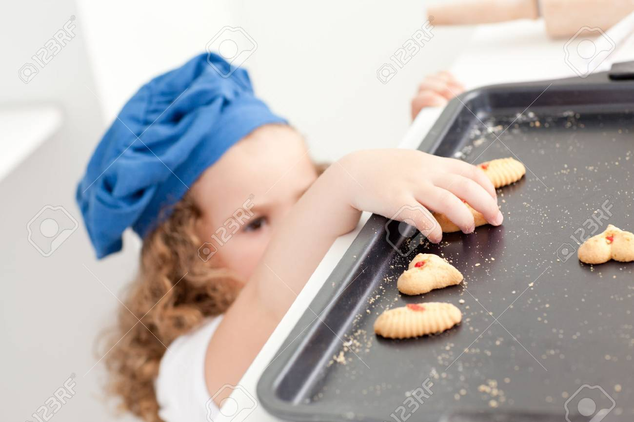 Little girl stealing cookies at home Stock Photo - 10220440