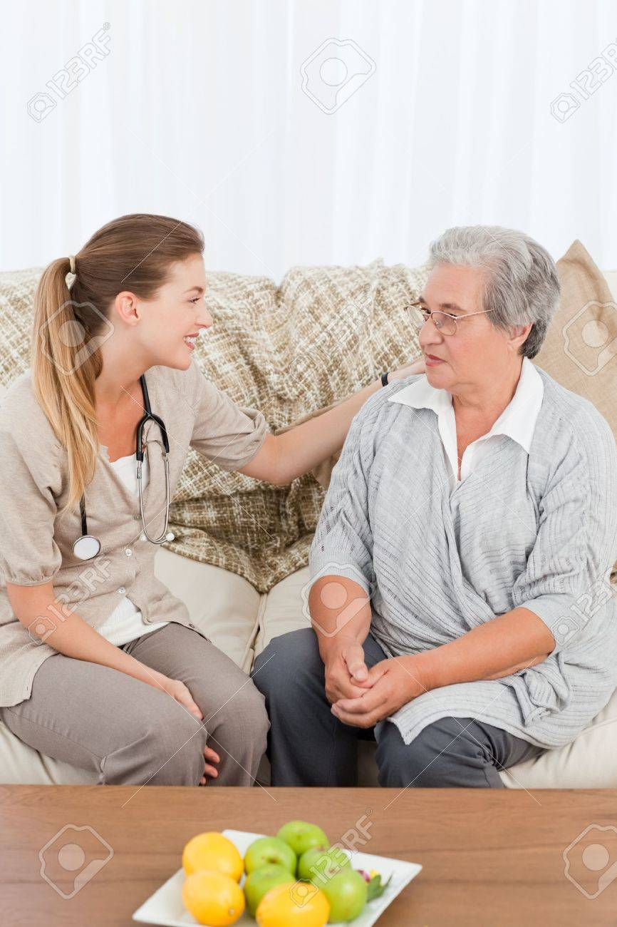 Nurse taking the heartbeat of her patient at home Stock Photo - 10220293
