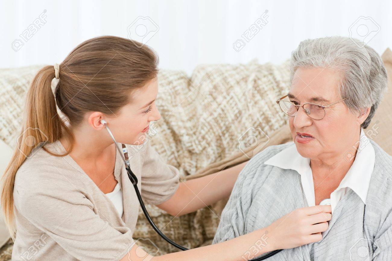 Nurse taking the heartbeat of her patient at home Stock Photo - 10220290
