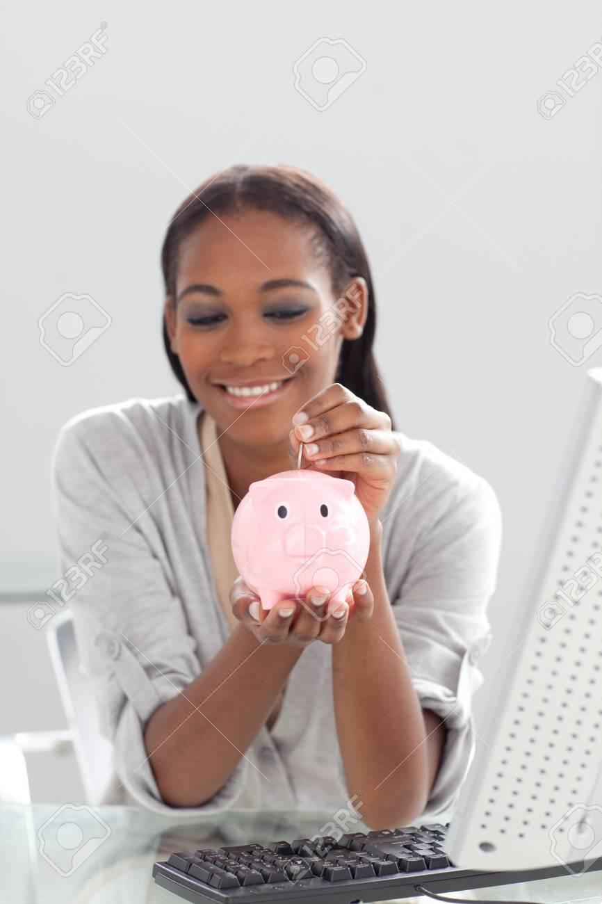 Afro-american businesswoman saving money in a piggybank Stock Photo - 10259334