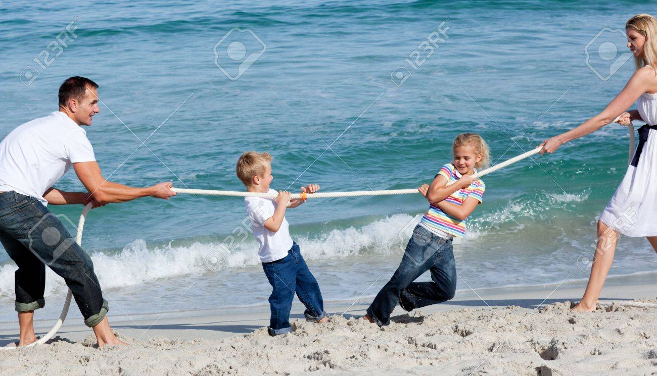 Happy family playing tug of war Stock Photo - 10222047