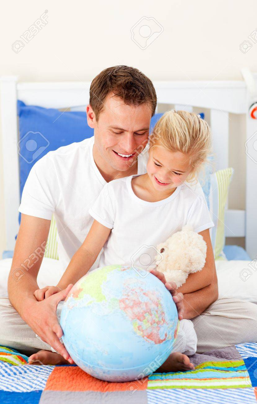 Earing father and his daugther looking at a terrestrial globe Stock Photo - 10259323