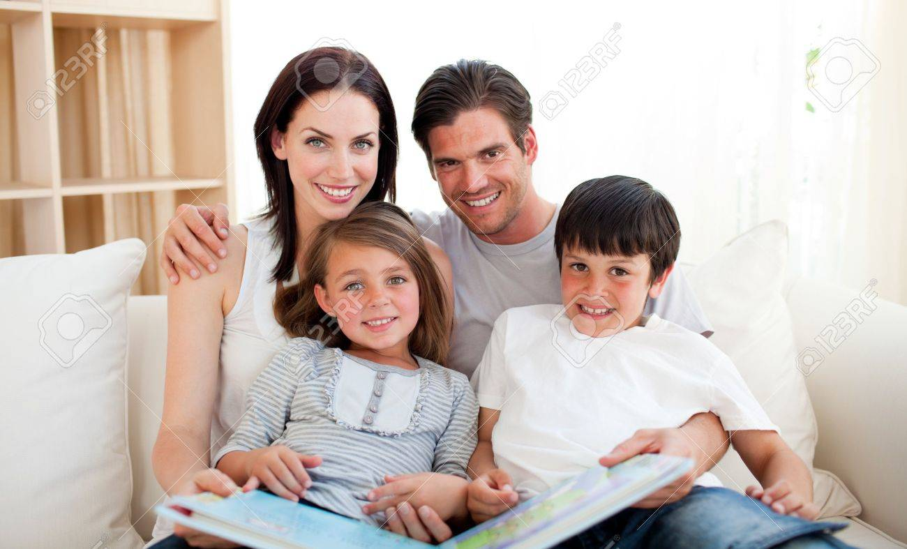 Family reading a book on the sofa Stock Photo - 10259054