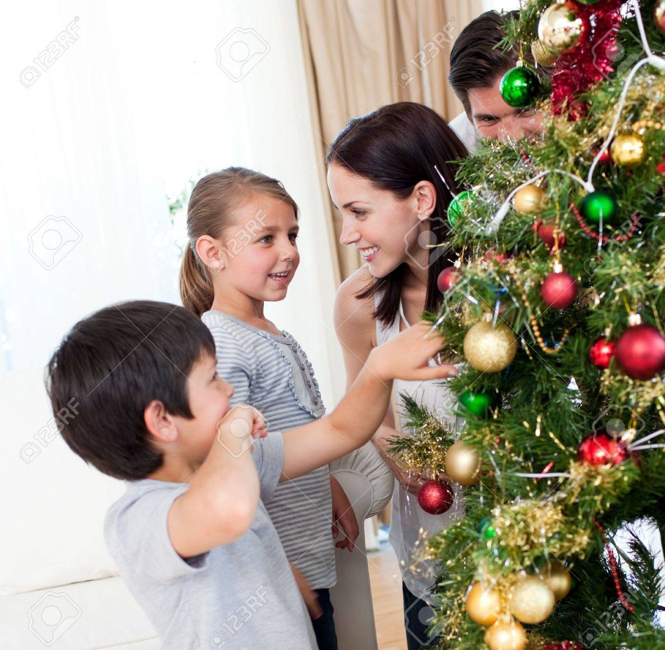 Smiling family decorating a Christmas tree with boubles Stock Photo - 10232471