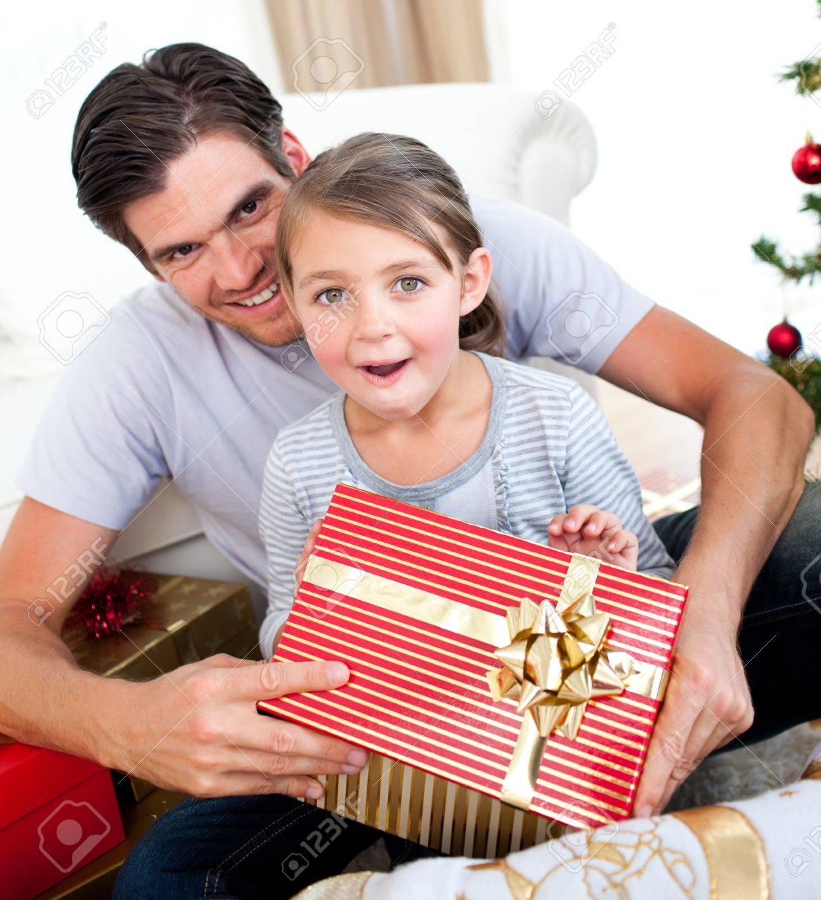 nia sorprendida abriendo un regalo de navidad con su padre foto de archivo