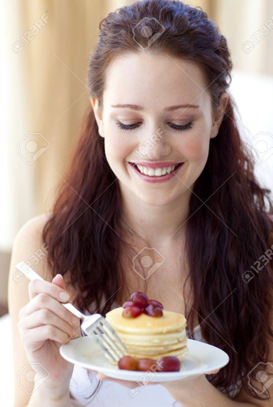Smiling woman eating a sweet dessert Stock Photo - 10257385