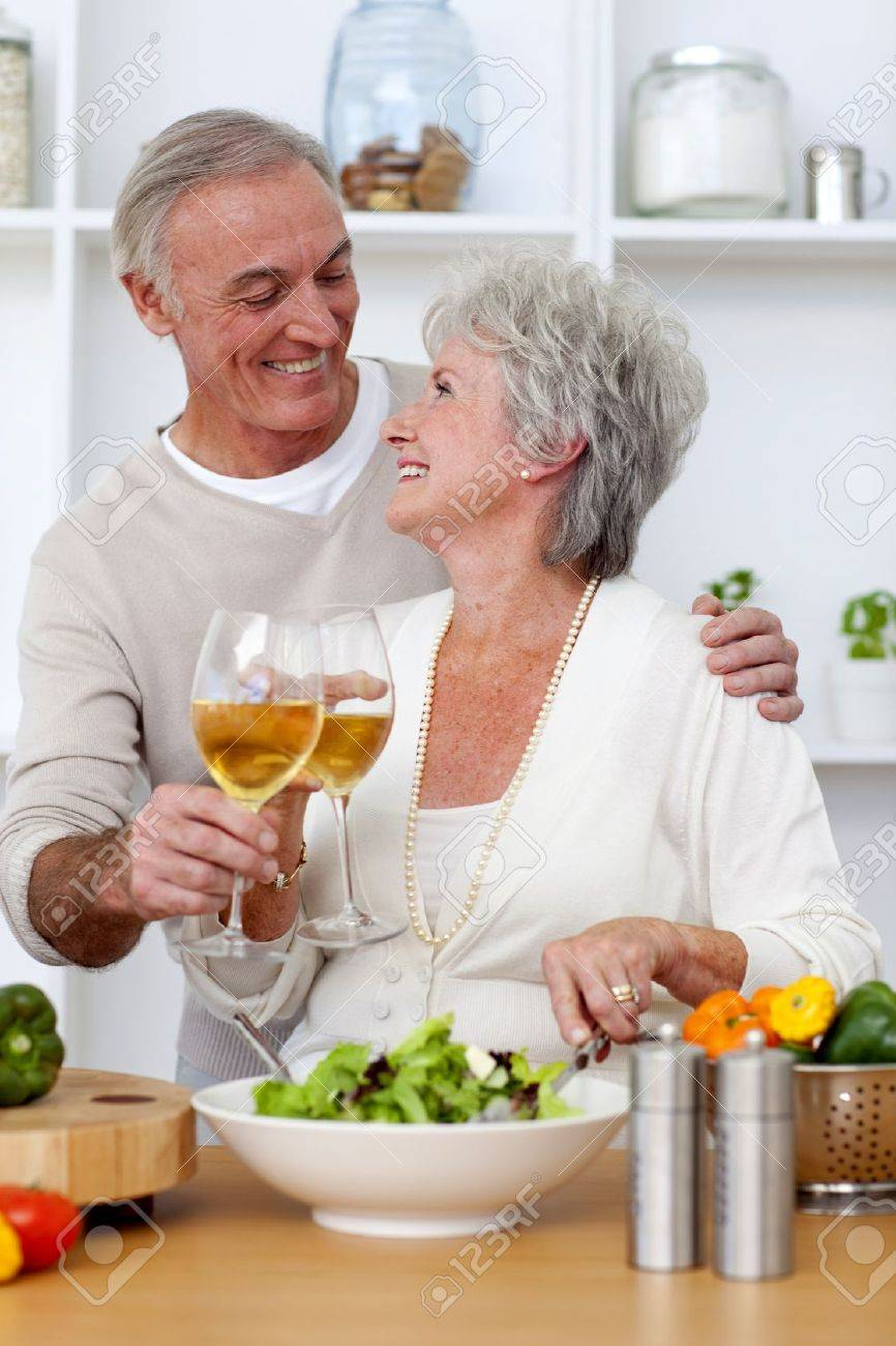 Senior couple in love eating a salad in the kitchen Stock Photo - 10240532