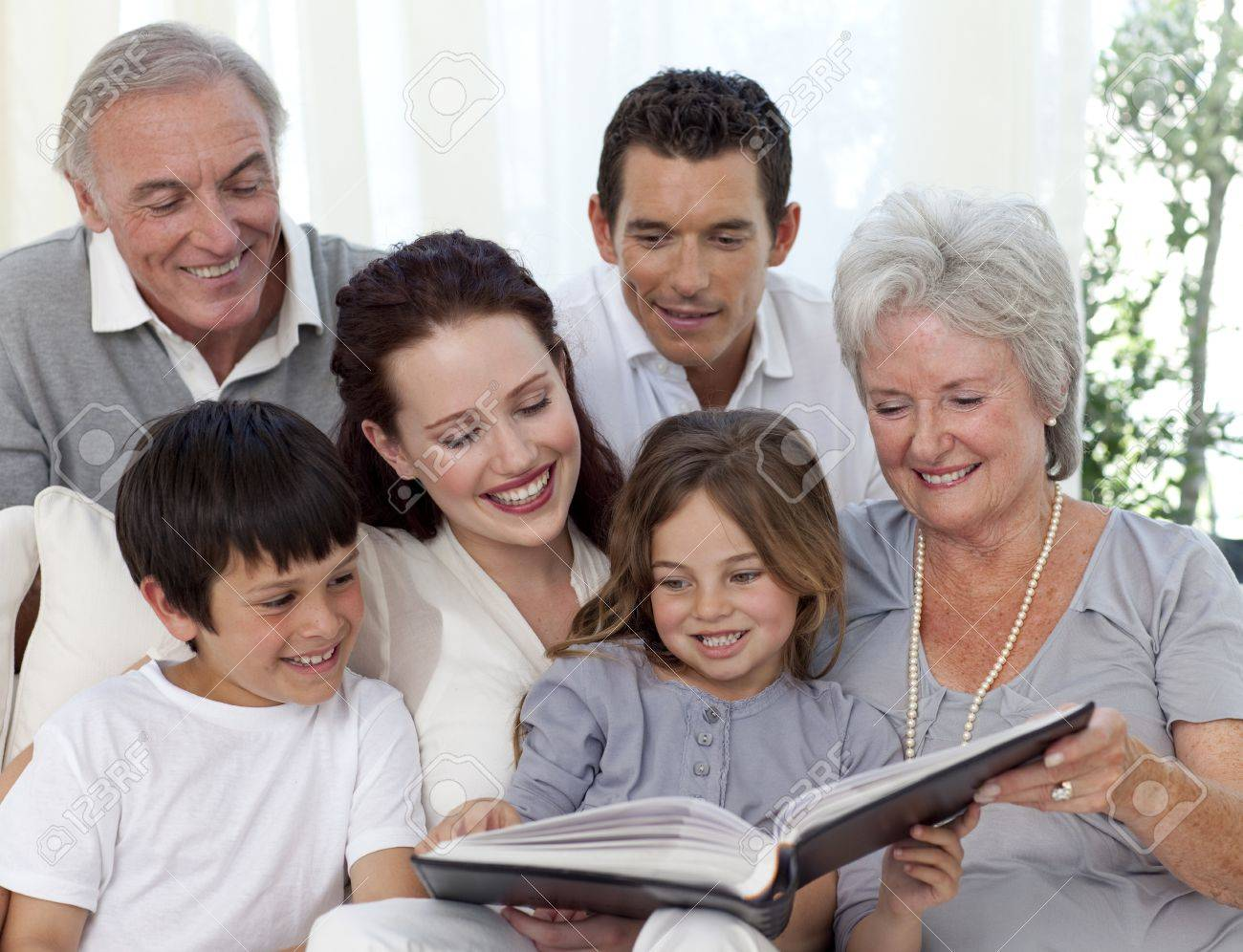 Family reading a book in living-room Stock Photo - 10239072