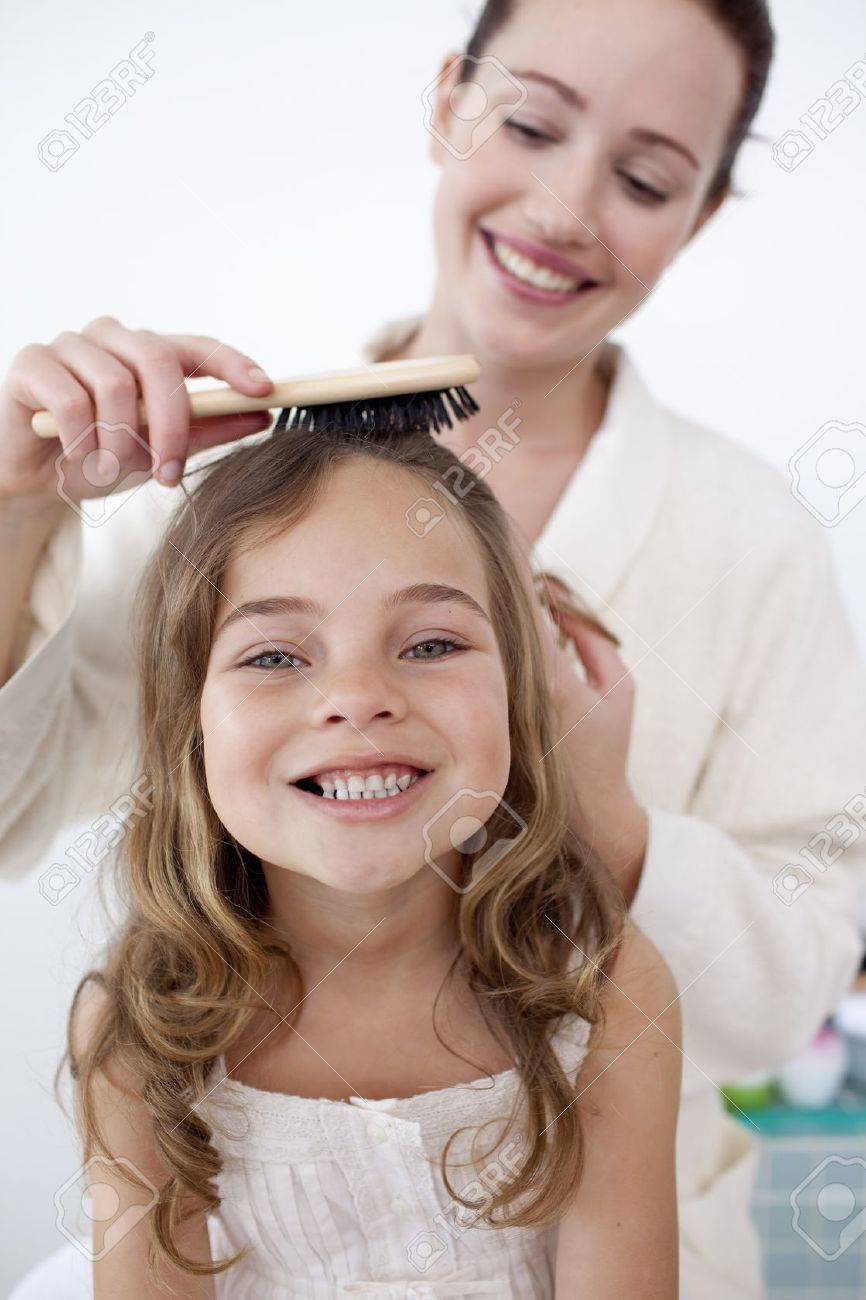 Portrait of mother doing her daughter's hair Stock Photo - 10258356