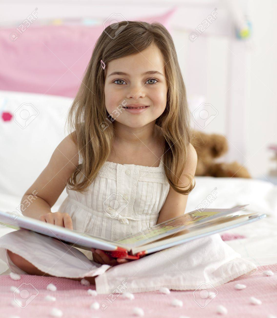 Smiling little girl reading in bed Stock Photo - 10244865