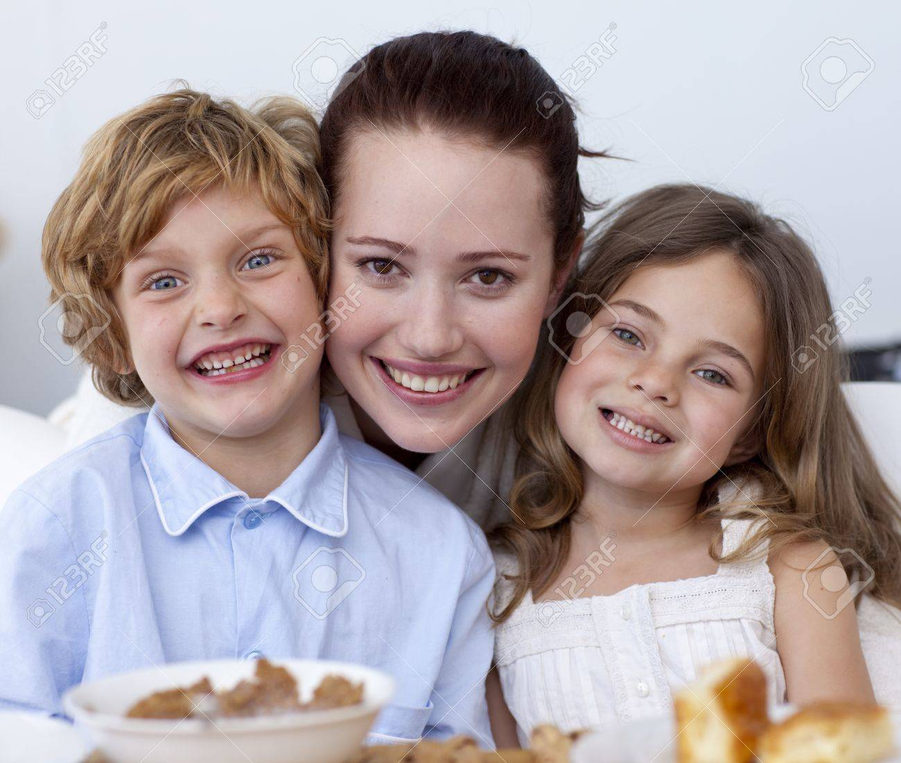 Portrait of children having breakfast with their mother Stock Photo - 10258458