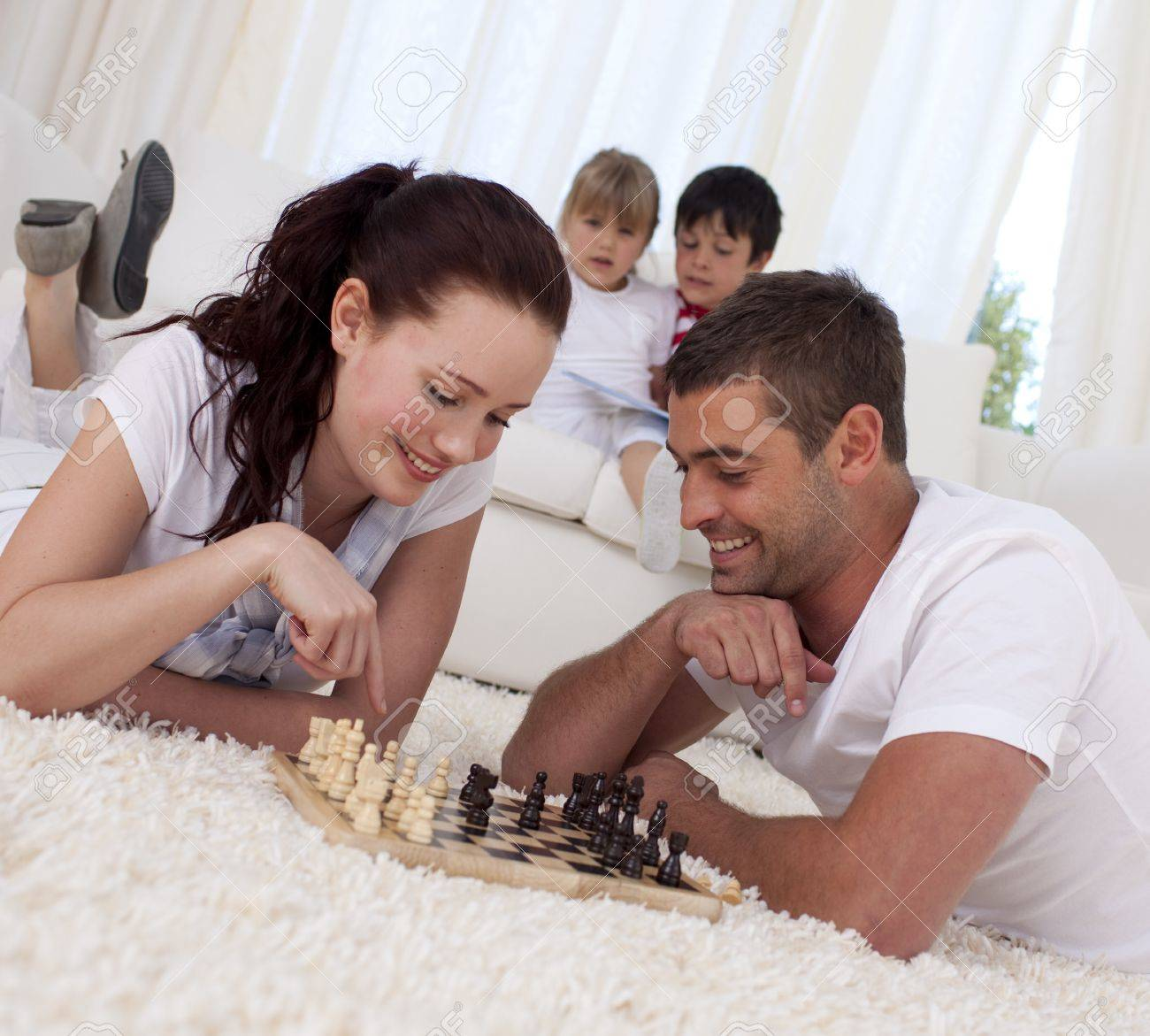 Smiling couple playing chess on floor in living-room Stock Photo - 10233735
