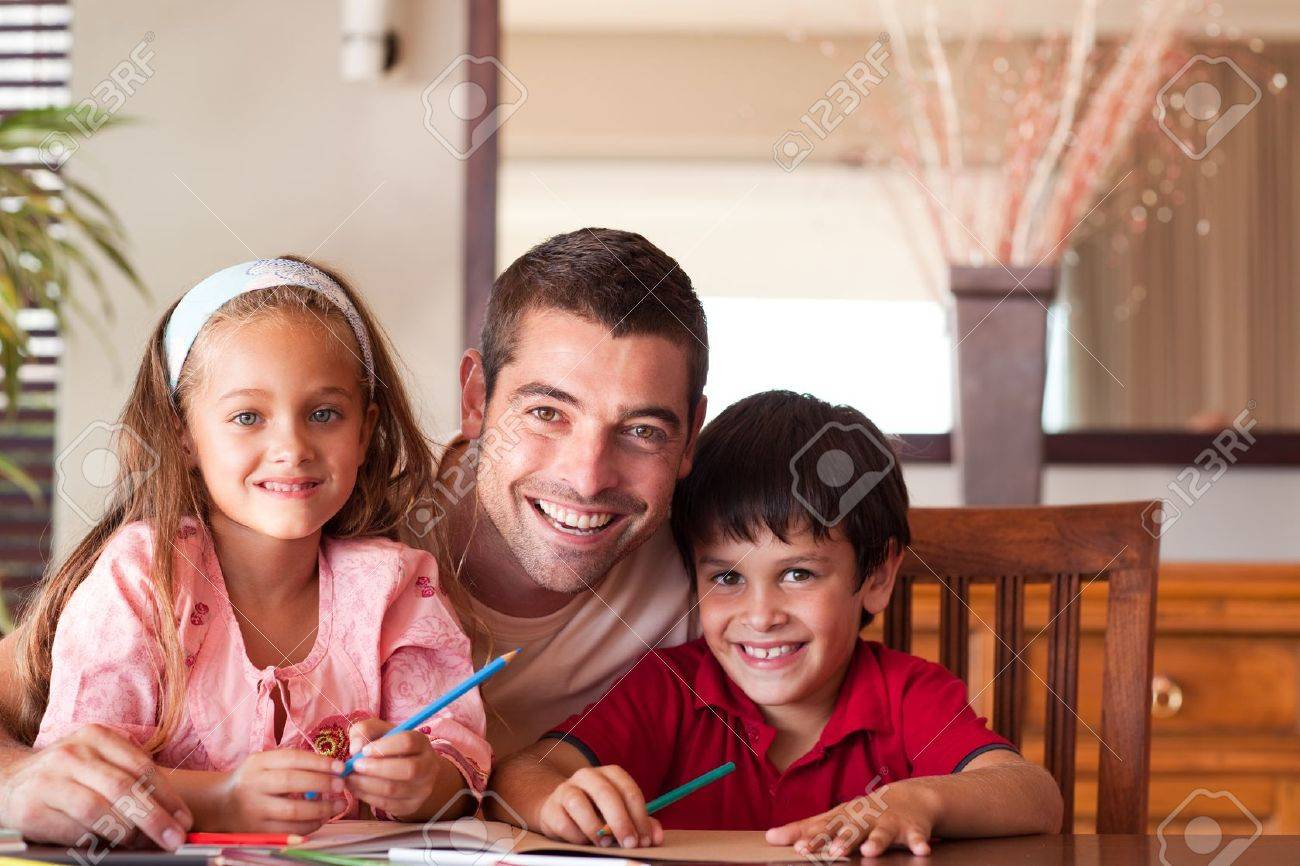 Radiant father helping his children for homework Stock Photo - 10249958