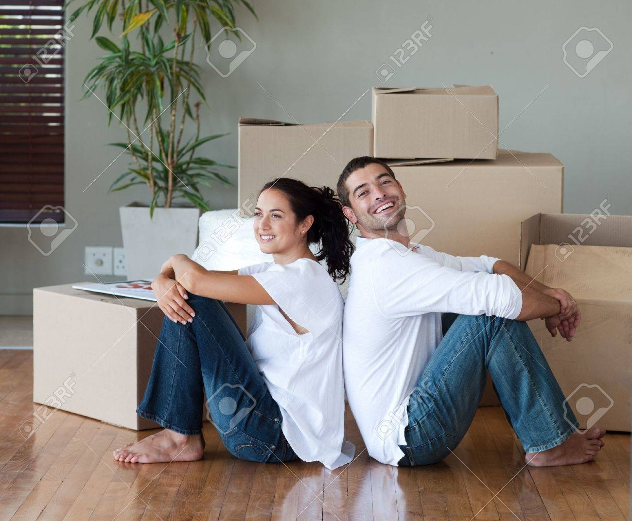 Bright couple with unpacking boxes moving to a new house Stock Photo - 10249839