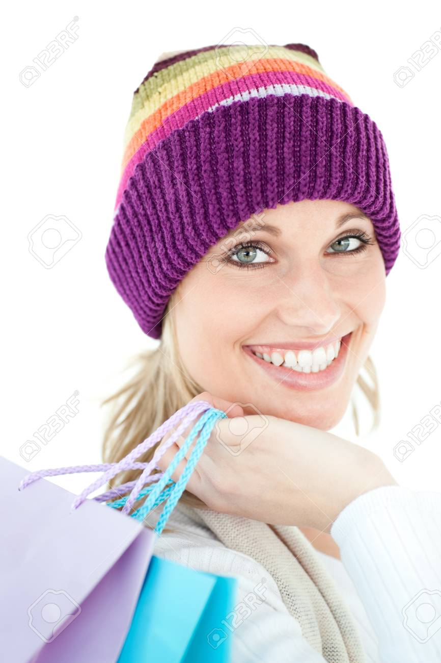 Bright woma holding shopping bags wearing a colourful hat against white background Stock Photo - 10248082