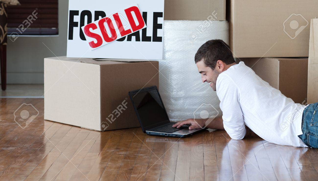 Beautiful man working at his laptop on the floor Stock Photo - 10249347