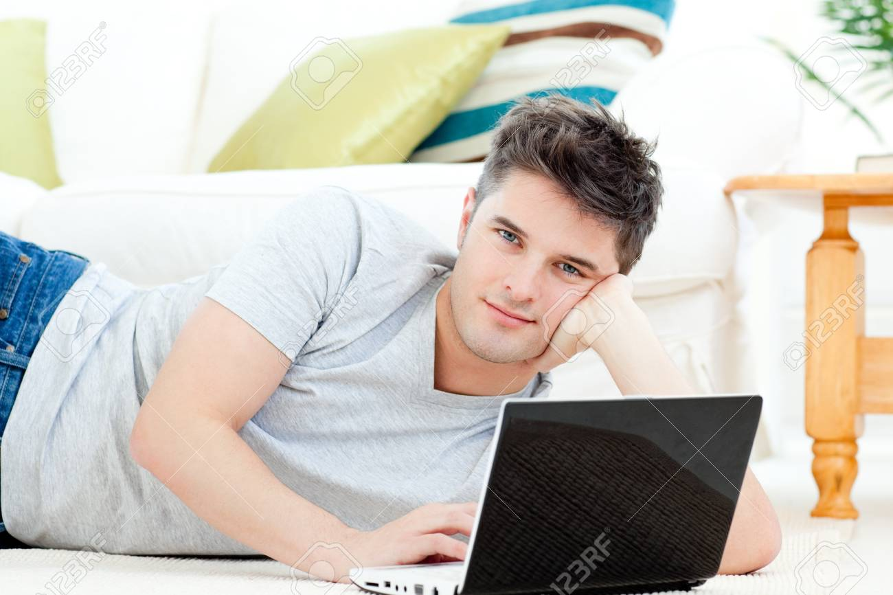 Handsome young man lying on the floor with a laptop Stock Photo - 10249453