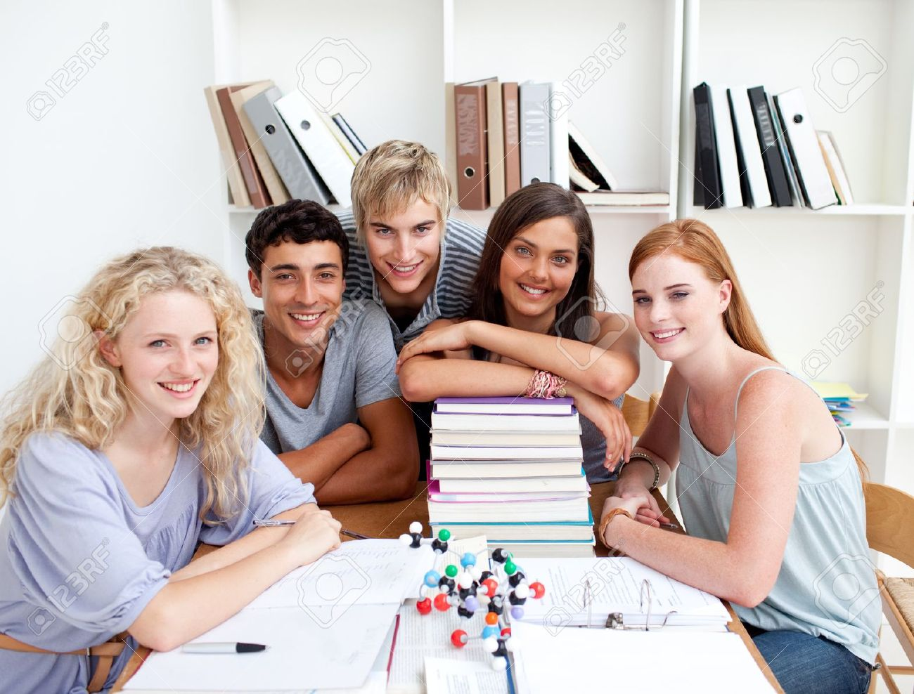 Smiling teenagers studying Science in a library Stock Photo - 10250362