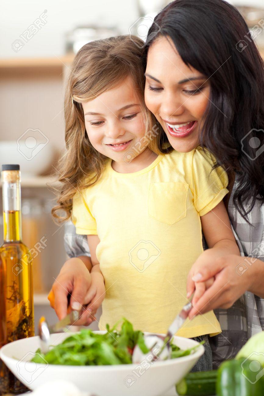 Brunette mother helping her daughter prepare salad Stock Photo - 10248730