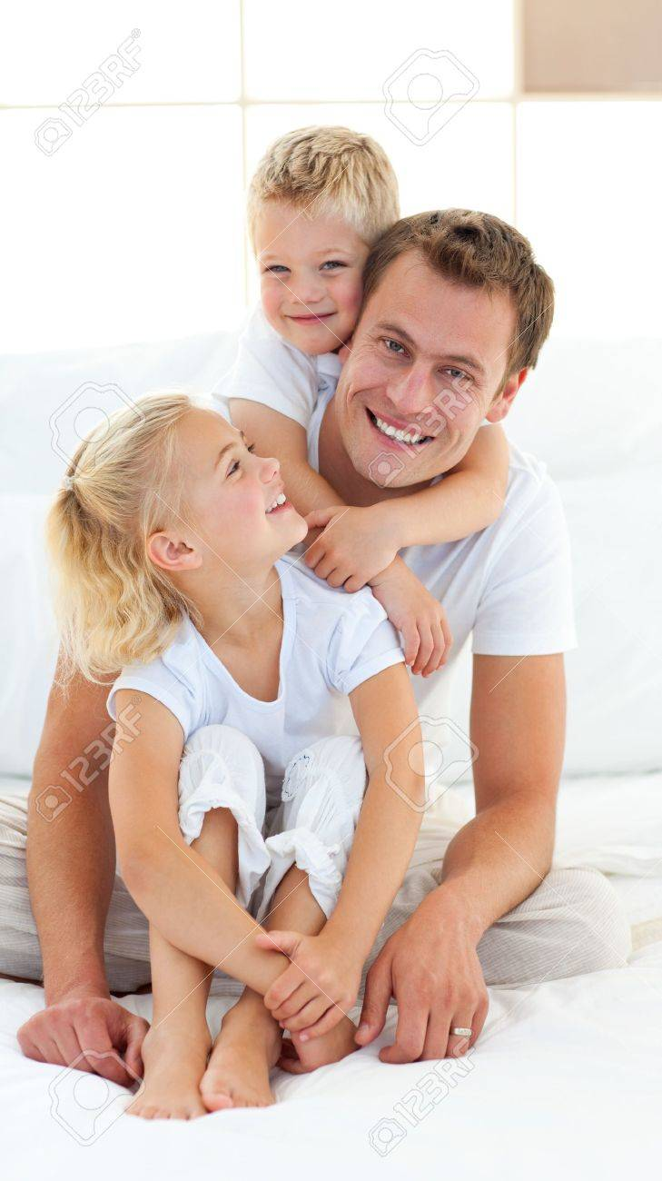 Caring father with his children sitting on bed Stock Photo - 10247497