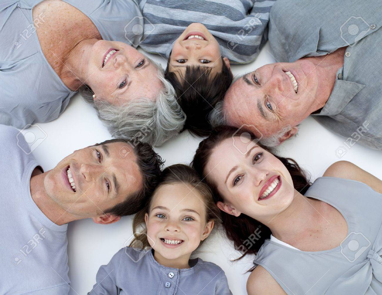 High angle of family lying on floor with heads together - 10248838