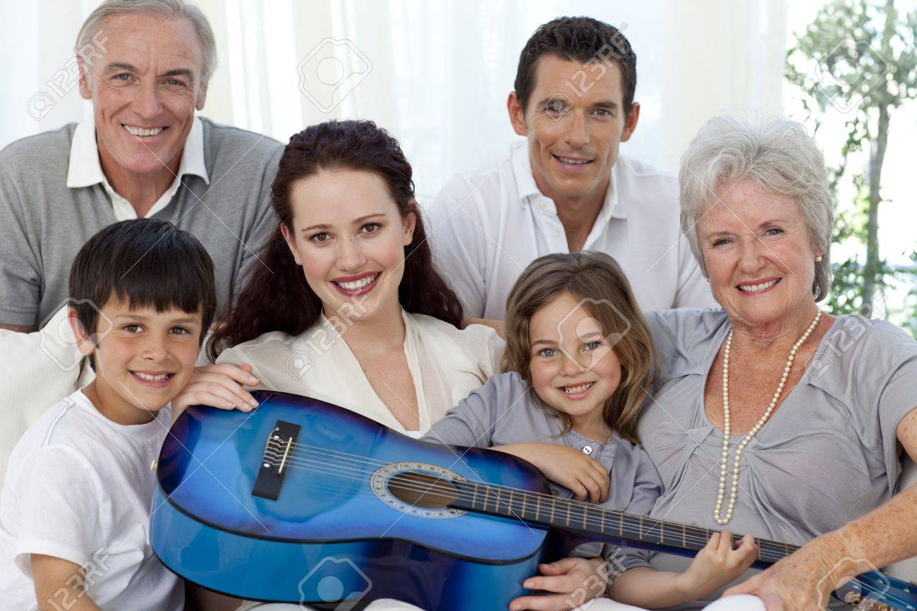 Portrait of family holding a guitar in living-room Stock Photo - 10250454