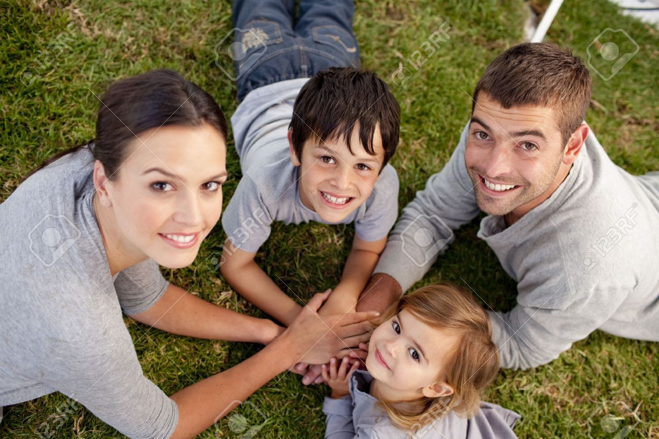 young Parents and kid lying on garden with hands together Stock Photo - 10249042