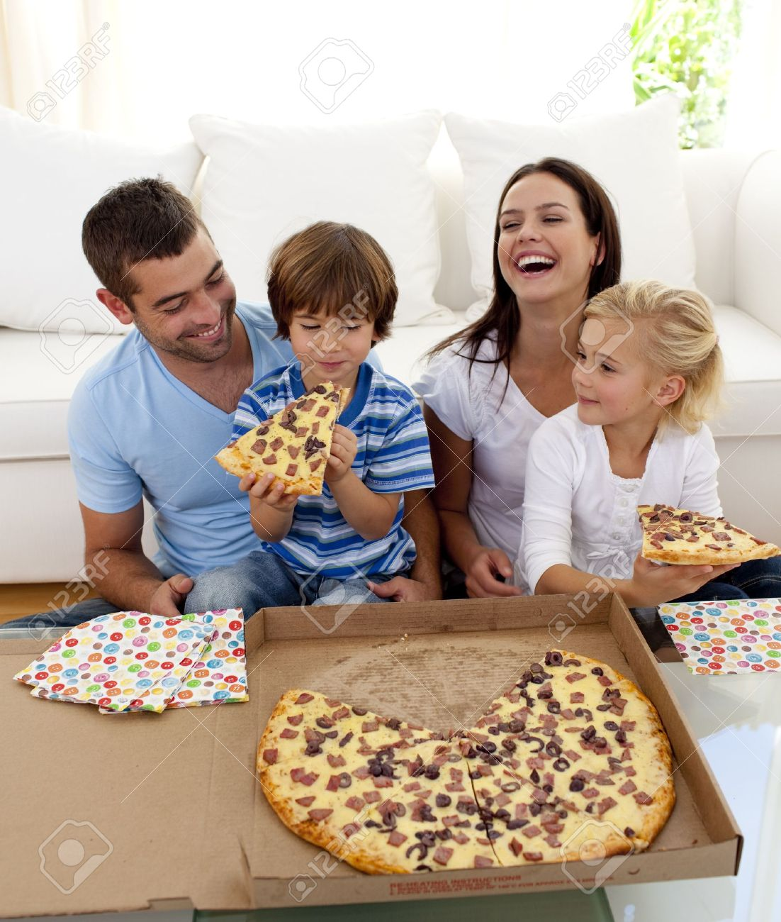 Parents and children eating pizza in living-room Stock Photo - 10249802