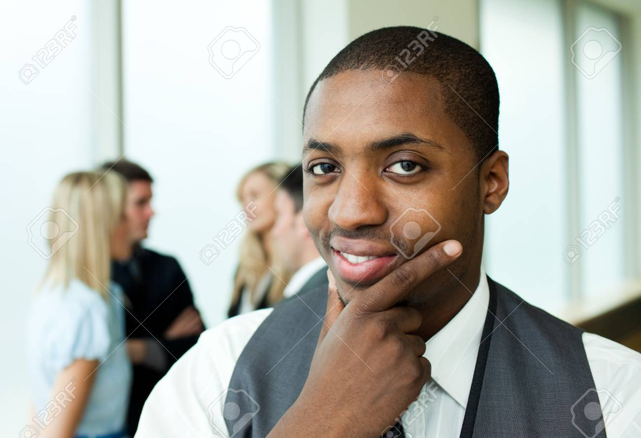 Thoughtful ethnic businessman smiling at the camera Stock Photo - 10246450