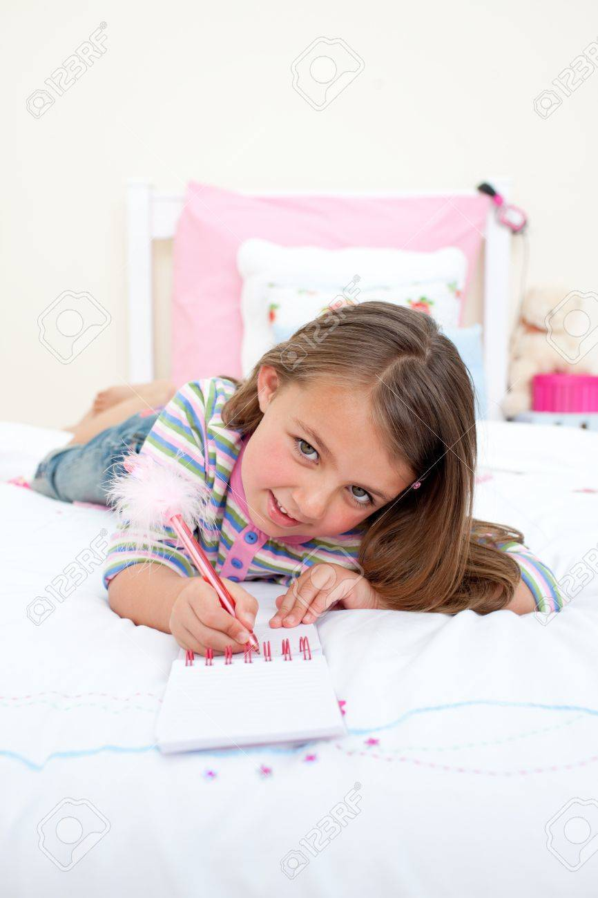 Cute Little girl writing on a notebook Stock Photo - 10249418